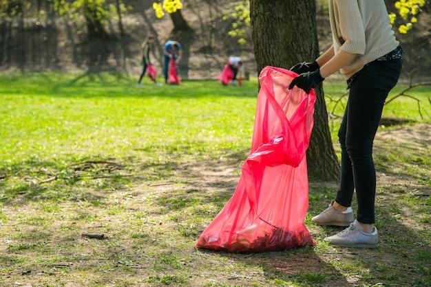 Volontario della donna che indossa la raccolta di rifiuti e rifiuti di plastica nel parco pubblico.