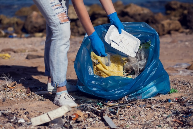 Volontario della donna in maglietta bianca con la grande borsa blu che raccoglie immondizia sulla spiaggia. concetto di inquinamento ambientale