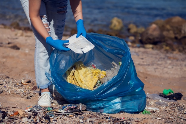 Volontario della donna con la grande borsa blu che raccoglie immondizia sulla spiaggia. concetto di inquinamento ambientale