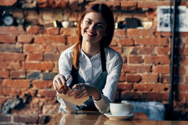 Cameriere della donna in uniforme del caffè vicino al tavolo