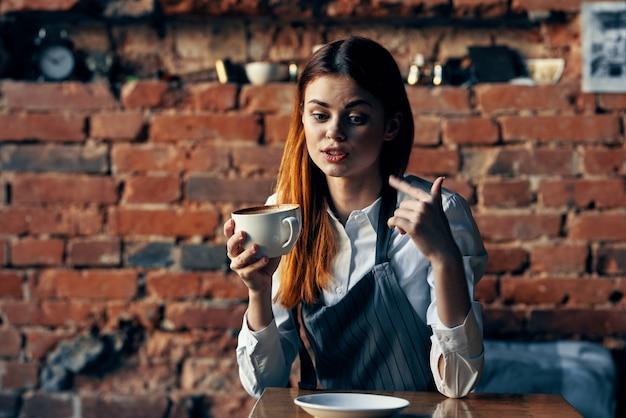 Donna cameriere tazza di caffè seduto al tavolo divertente lavoro