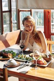 Donna che aspetta ragazzo nel ristorante