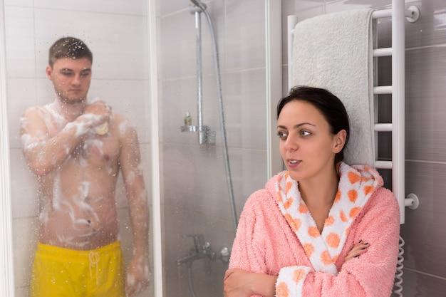 Donna che aspetta il suo ragazzo mentre si strofina una spugna da bagno in schiuma nella cabina doccia con porte in vetro trasparente in bagno