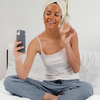 Donna che aspetta che la sua maschera per il viso faccia il suo effetto