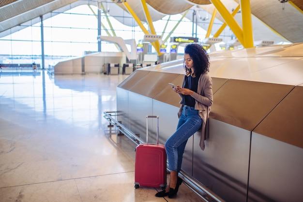 Donna che aspetta il suo volo facendo uso del telefono cellulare all'aeroporto