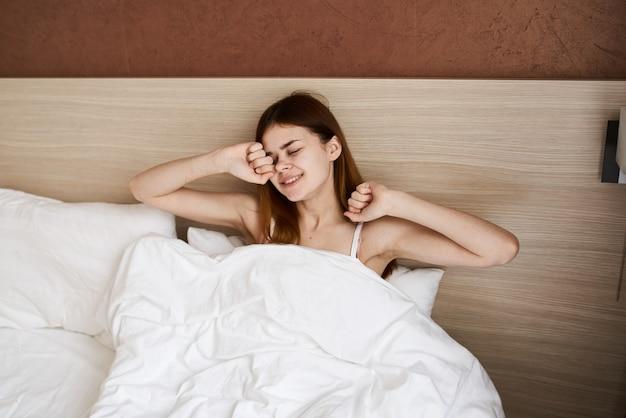 Donna che si sveglia la mattina presto sotto le coperte a letto