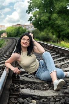 La donna cammina sui binari della ferrovia, viaggio di stile di vita estivo