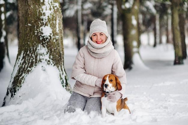 Una donna in una passeggiata con il suo cane nella foresta invernale. padrona e gioco del cane nella foresta innevata.
