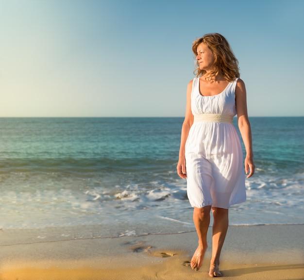 Donna che cammina lungo la spiaggia guardando il sole