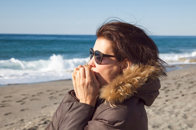 Donna che cammina lungo la spiaggia in inverno.
