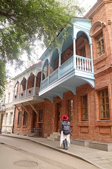 Donna che cammina lungo una strada stretta con edifici tradizionali georgiani nella città vecchia di tbilisi, georgia