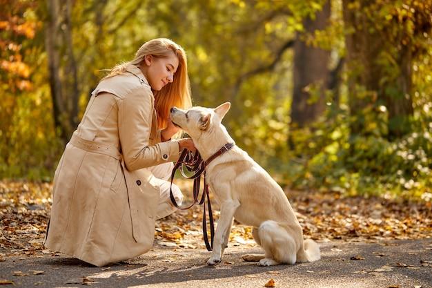 Donna che cammina nella foresta di autunno con il compagno di cane