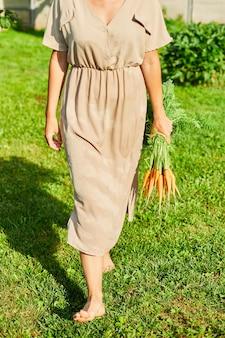 Donna che cammina a piedi nudi sull'erba e tiene in mano un ramo di carote organiche crude