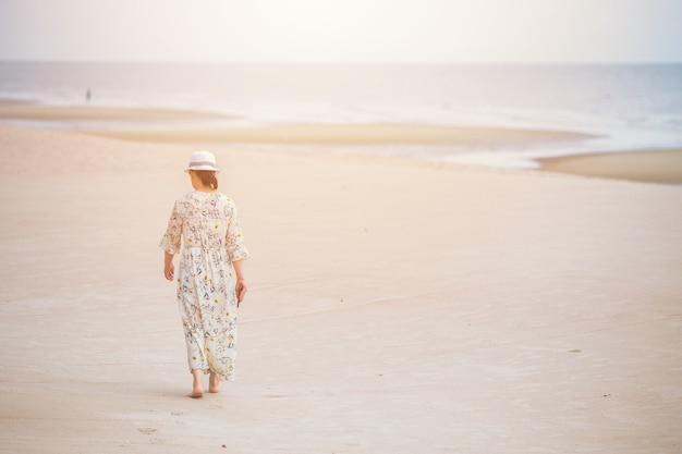 Donna che cammina da sola sulla spiaggia da sola con spazio per il testo