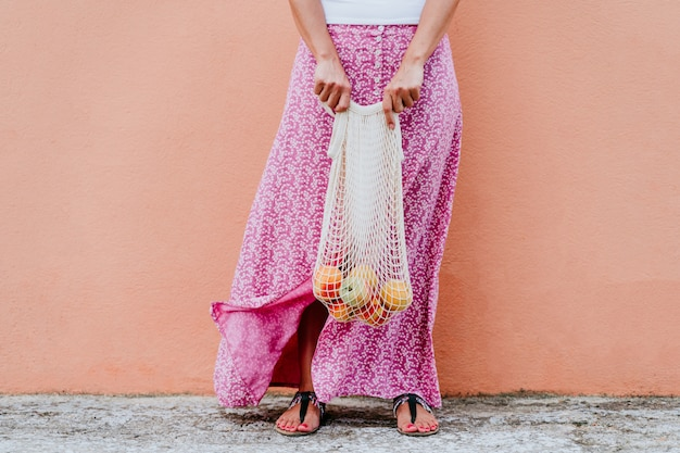 Donna che cammina per la città, tenendo in mano un sacchetto di cotone con frutta.