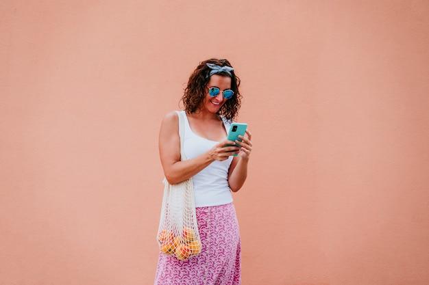Donna che cammina per la città, utilizzando il telefono cellulare e tenendo un sacchetto di cotone con frutta.