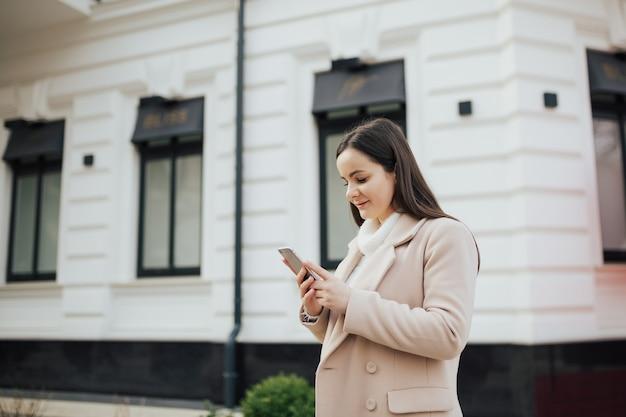Donna che cammina in città e utilizza lo smartphone