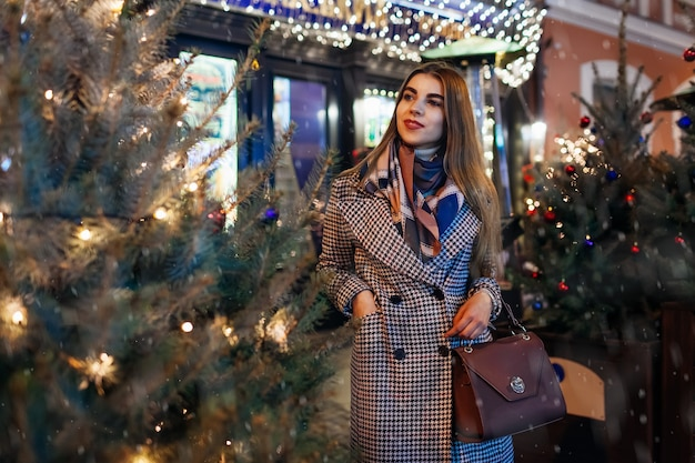 Donna che cammina sulla strada della città da alberi di natale decorati. ragazza alla moda che gode dell'atmosfera di vacanza sotto la neve che cade