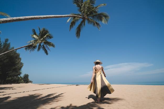 Donna che cammina sotto la palma da cocco sulla spiaggia sabbiosa con cielo blu.
