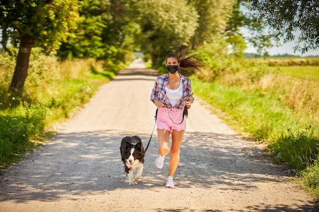 Donna che porta a spasso un cane in campagna e indossa una maschera