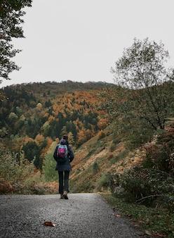 Donna che cammina lungo una strada di montagna escursioni nella foresta di irati in autunno