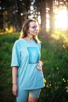 Donna che cammina all'inizio nella zona della foresta estiva