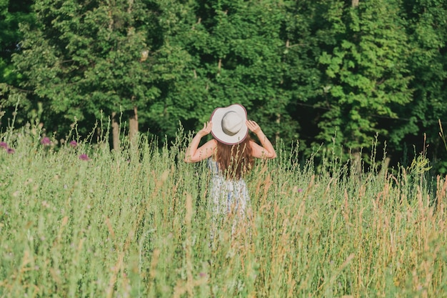 Donna che cammina in un campo in una giornata di sole estivo vista sul retro