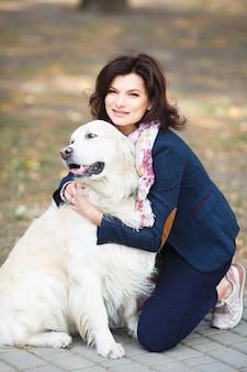 Donna che cammina labrador retriever nel parco. ragazza con cane per strada