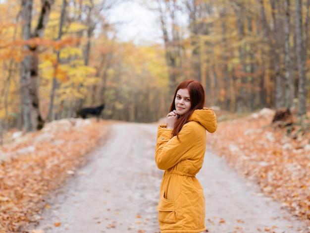 Donna che cammina nella natura autunno alberi strada nuvoloso tempo