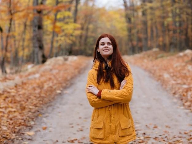 Donna che cammina nella natura autunno alberi strada nuvoloso meteo