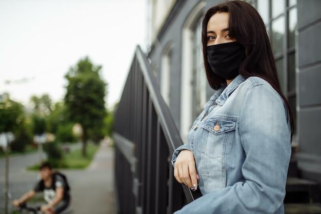 Donna che cammina all'aperto indossando maschera protettiva