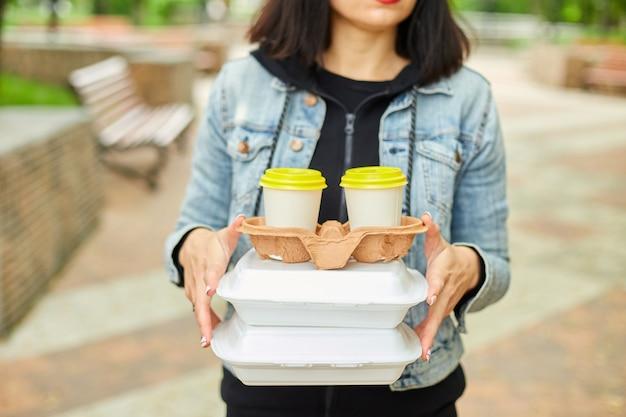 Donna che cammina nel parco, con in mano cibo e caffè da asporto, in pausa pranzo dal lavoro.