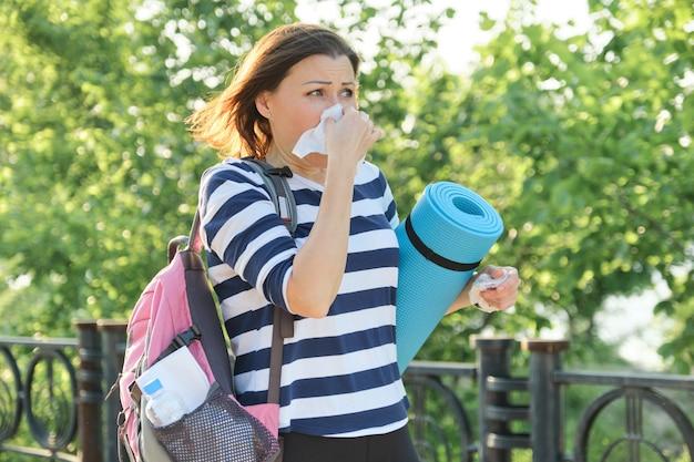 Donna che cammina nel parco con fazzoletto, tosse e starnuti