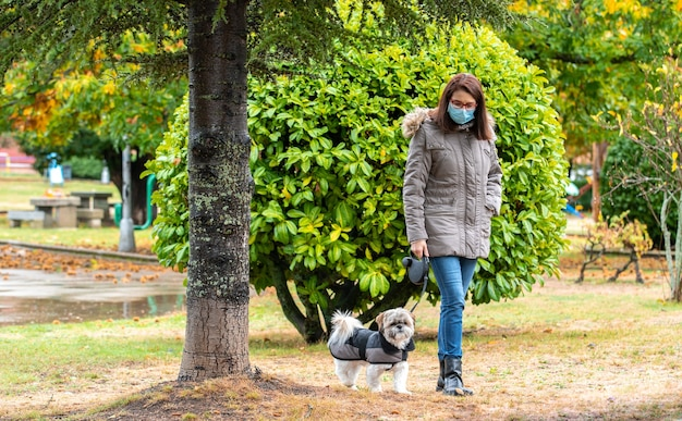 Donna che cammina nel parco con il suo cane sotto la pioggia