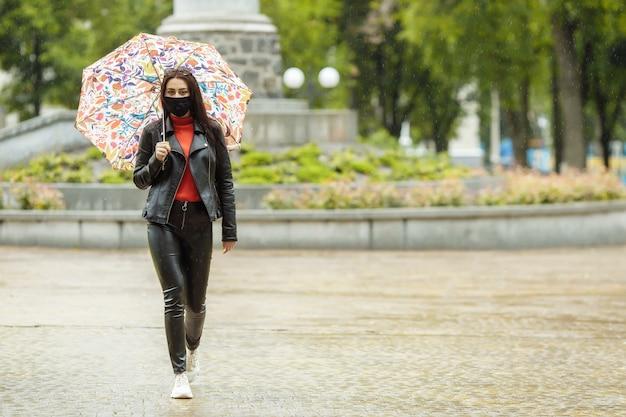 Donna che cammina per strada indossando maschera protettiva