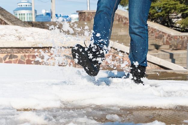 Donna che cammina nella neve spargendola in giro