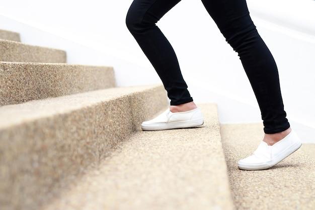 Donna che cammina su per le scale in un edificio per uffici