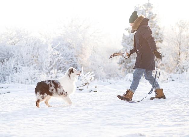 Donna che cammina con il cane da pastore australiano nella foresta di inverno