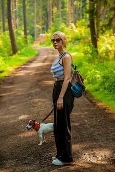 Donna che cammina con un cane in una foresta in polonia