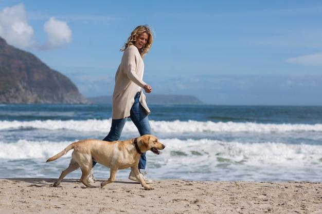Donna che cammina con il suo cane sulla spiaggia