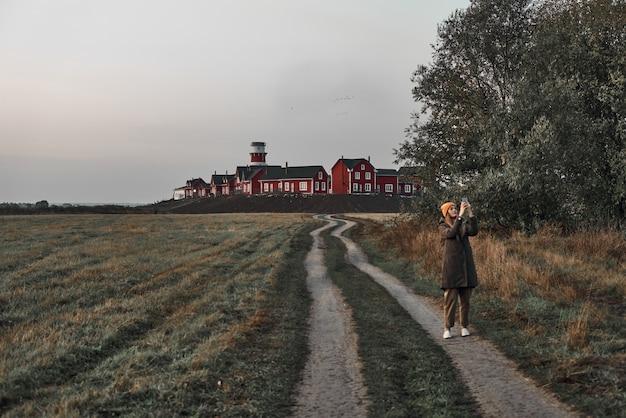 Una donna cammina lungo una strada di campagna, un faro rosso e bianco alla fine della strada. viaggio, alba.