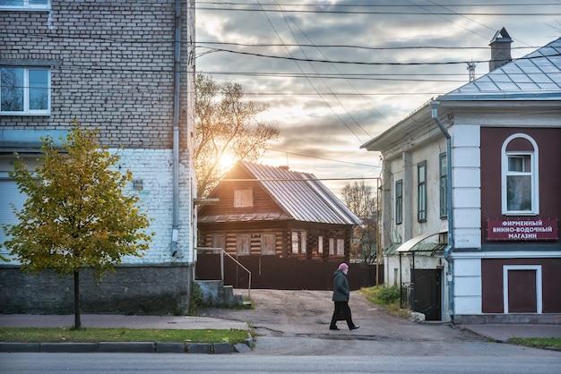 Una donna cammina tra case nuove e vecchie a uglich