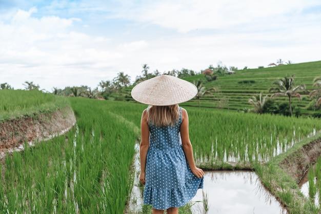 Una donna cammina sulle terrazze di riso a bali