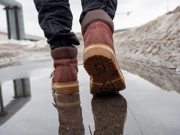 Una donna cammina attraverso una pozzanghera con scarpe di cuoio di terracotta. primo piano, riflesso in una pozzanghera, orizzonte disseminato. concetto di uomo che cammina, viaggio