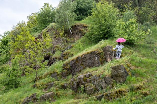 Una donna cammina sotto un ombrellone in montagna, tra le rocce ricoperte di verde.