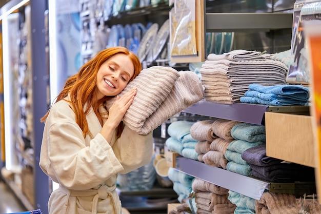 La donna vuole comprare un asciugamano, la femmina indossa l'accappatoio, abbraccia l'asciugamano, si sdraia su di esso nel corridoio del supermercato