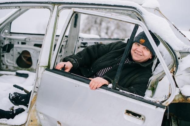 La donna in vestiti caldi si siede nella vecchia automobile