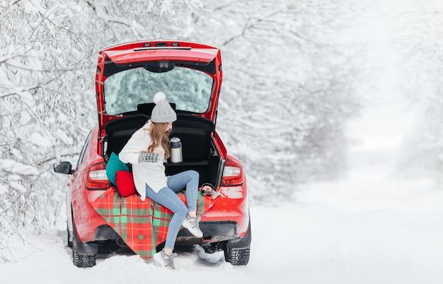 Donna in abiti caldi seduti nel bosco invernale mentre si appoggia alla macchina e tiene una tazza di caffè.