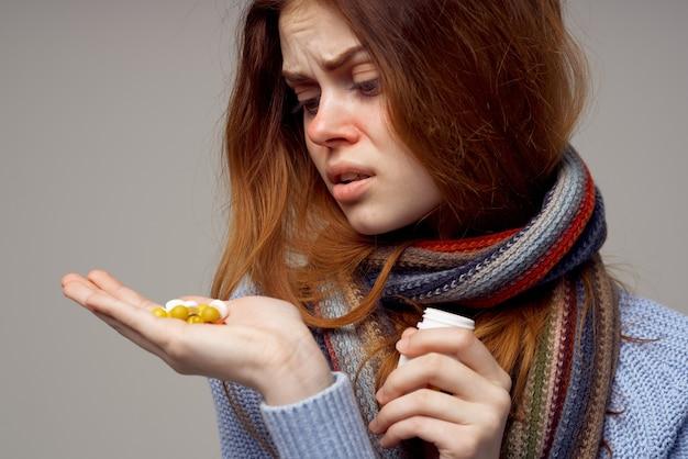 Donna in vestiti caldi con le pillole in mano problemi di salute vitamine vaso bianco