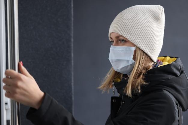 Donna in abiti caldi e maschera protettiva aggrappata alla maniglia della porta all'esterno